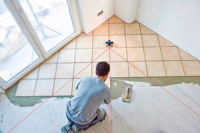 Процесс укладки плитки на полу