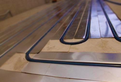 Укладка водяных турб на фольгу на деревянном полу