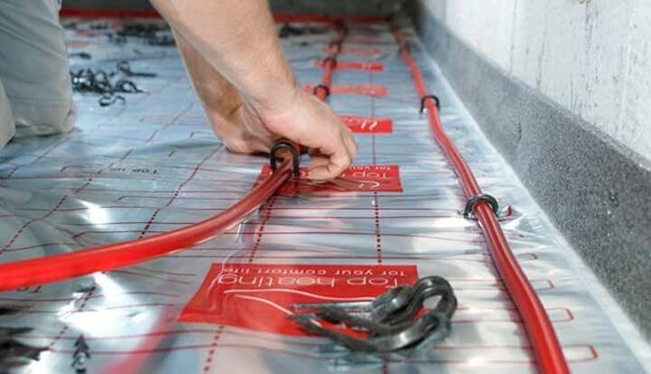 К арматурной сетке, трубы крепятся при помощи хомутов или проволоки